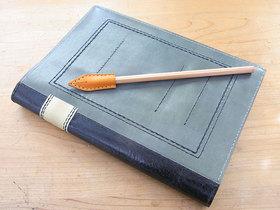 ノート型ノートカバーの上にペン先型ペンシルキャップ